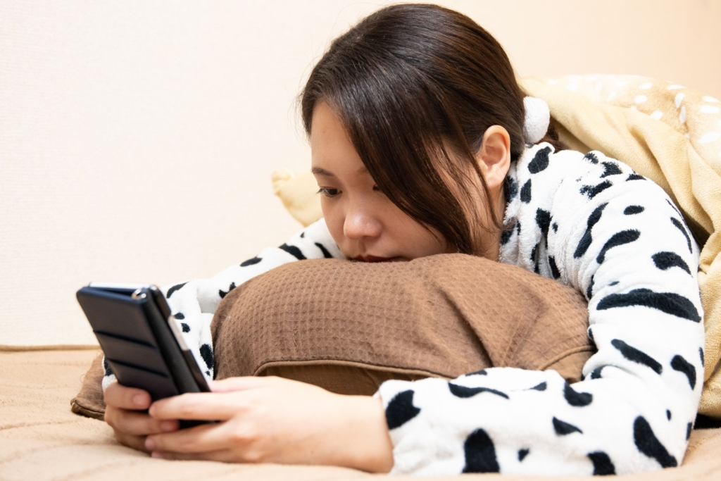 寝る前にベッドでスマートフォンを見る女性
